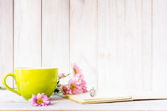 Notebook with a pencil on the table next to coffee and flowers. Stock Photos