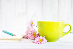 Notebook with a pencil on the table next to coffee and flowers. Royalty Free Stock Images