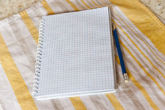 A notebook and a pencil on a towel. Notebook made of paper and a pencil on a towel royalty free stock photos