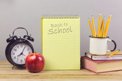 Notebook with pencils, apple and alarm clock on wooden table. Back to school Stock Images