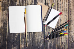 Notebook with pencils. And brushes on a wooden background Royalty Free Stock Photos