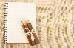 Notebook and pencils on burlap Royalty Free Stock Image