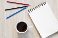 Notebook,pencils and cup of coffee on table. stock photography