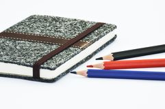 Notebook and pencils. A dark notebook with several pencils Stock Image