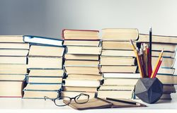 Notebook, pencils, glasses and stack of books, school background for education learning concept.  stock image
