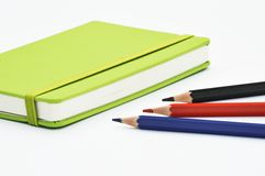 Notebook and pencils. A green notebook with several pencils Stock Photos