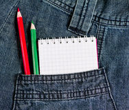 Notebook and pencils in jeans pocket Royalty Free Stock Image