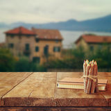 Notebook and pencils on old wooden table in front of romantic Provence rural landscape. retro filtered image.  Stock Images