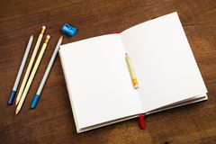 Notebook and Pencils. Opened notebook with pencils on wood background Stock Photos