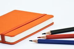 Notebook and pencils. An orange notebook with several pencils Royalty Free Stock Images