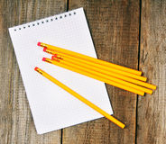 Notebook and pencils on wooden background. Royalty Free Stock Photo