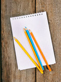 Notebook and pencils on wooden background. Royalty Free Stock Photos