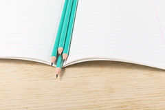 Notebook with pencils and on a wooden surface Royalty Free Stock Photo