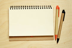 Notebook and pens on desk. Notebook and pens on wooden desk royalty free stock photography