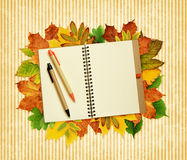 Notebook and pens on dry autumn leaves Royalty Free Stock Photos