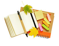 Notebook and pens with dry autumn leaves Stock Images
