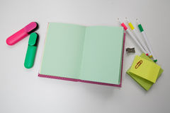 Notebook among the pens and markers Royalty Free Stock Images