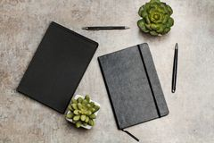 Notebook, pens and plants on a table. Notebook, pens and plants on a marble table stock photo