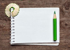 Notebook with pensil. And pencil shavings on wooden background Stock Images