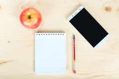 A notebook a phone and an apple on the table Royalty Free Stock Image