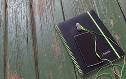 Notebook and phone with headphones on green wood table. Relax growing ideas Stock Image