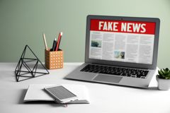 Notebook, phone and laptop with words FAKE NEWS on screen in room royalty free stock photo