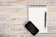 Notebook and phone on wood table for  background Royalty Free Stock Images
