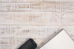 Notebook and phone on wood table for text and background Royalty Free Stock Photos
