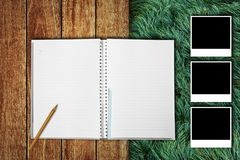 Notebook with photo frames on wooden floor and grass field Royalty Free Stock Photos