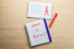 Notebook with phrase. `What is autism?` and drawing on light background Stock Photo
