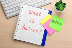 Notebook with phrase. `What is autism?` on table Royalty Free Stock Photo