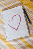 A notebook with pictured heart on a table. Notebook made of paper with pictured heart on a table royalty free stock photo