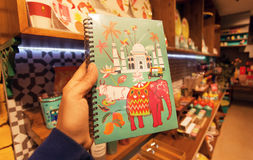 Notebook with pictures from India - Taj Mahal, cow, elephant on cover in bookstore. BANGALORE, INDIA - FEB 14: Notebook with pictures from India - Taj Mahal, cow Stock Photography