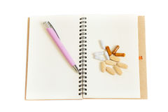 Notebook and pills on white. Royalty Free Stock Images