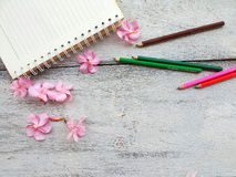 notebook pink flowers and pencil on wood background Stock Image