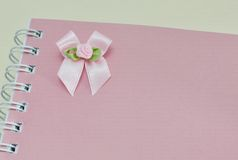 Notebook and pink ribbon bow Stock Image