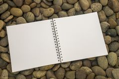 Notebook that is placed on a pile of stones stock image