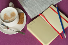 Notebook with plans, morning coffee with milk foam and  newspape Stock Image