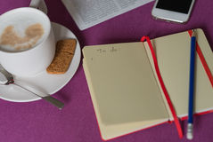 Notebook with plans, morning coffee with milk foam, smartphone a Royalty Free Stock Photos