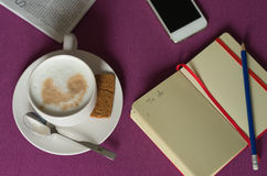 Notebook with plans, morning coffee with milk foam, smartphone a Stock Photos