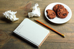 Notebook with plans for next year. A notebook with a record and a pencil near the saucer with biscuits on wooden background Royalty Free Stock Photos