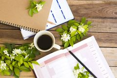 Notebook project year planner ,calendar book for business work. With hot coffee espresso  ,white flowers jasmine arrangement flat lay style on background wooden royalty free stock photography