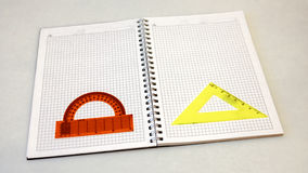 A notebook and a protractor on a light background stock photo