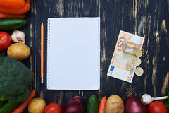 Notebook for purchase with money surrounded with raw organic veg Stock Photos
