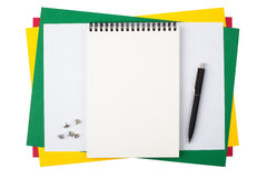 Notebook, push pins and a black pen on colored paper Royalty Free Stock Images
