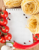 Notebook for recipes. Vegetables, spices and pasta on wooden table Stock Photos