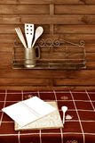 Notebook of recipes in country kitchen. Blank book recipes and shelves with utensils rustic style Stock Photography