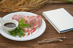 Notebook for recipes and raw pork with spices. On wooden table Royalty Free Stock Photo