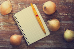 Notebook for recipes. And ripe onions on a wooden background. Top view . Concept of healthy with vegetables. Space for text. Toned image Royalty Free Stock Images