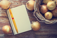 Notebook for recipes. And ripe onions on a wooden background. Top view . Concept of healthy with vegetables. Space for text. Toned image Royalty Free Stock Photography